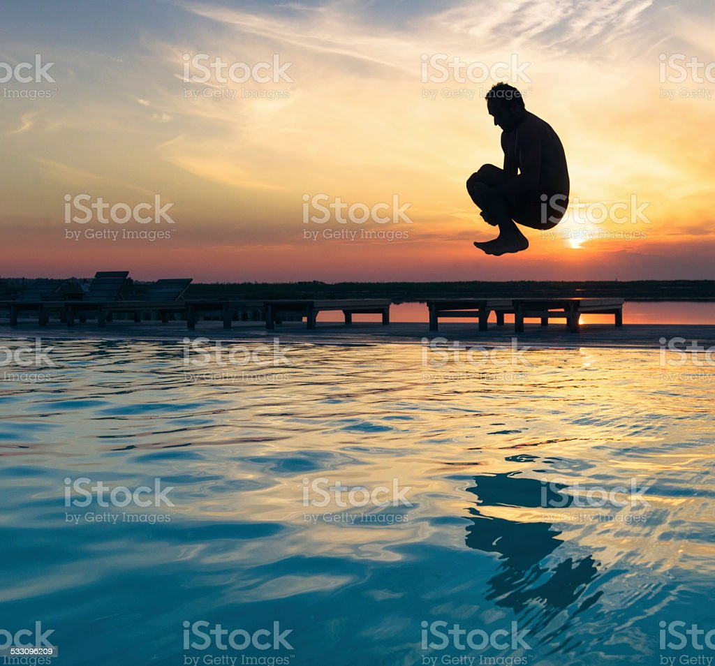 Dive-bombing the swimming pool stock photo