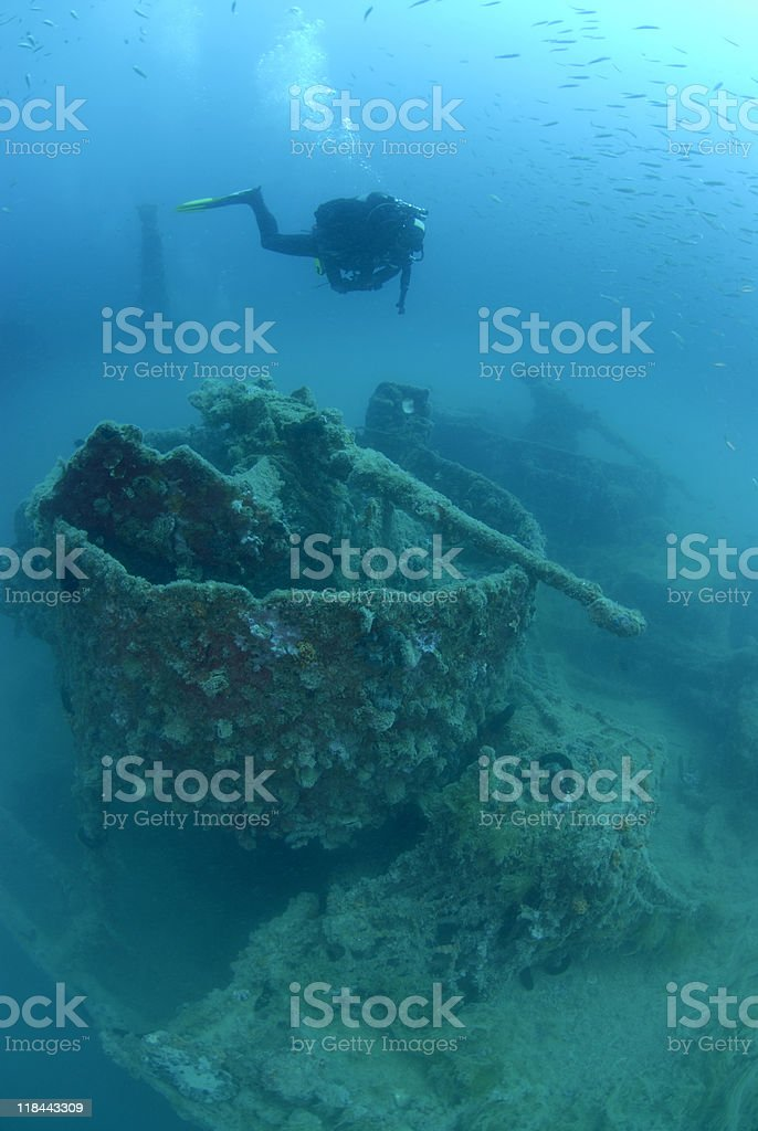 Diver exploring wreck with cannon stock photo