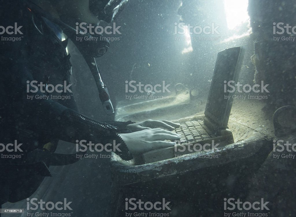 Diver in a submerged and ruined airplane using laptop stock photo