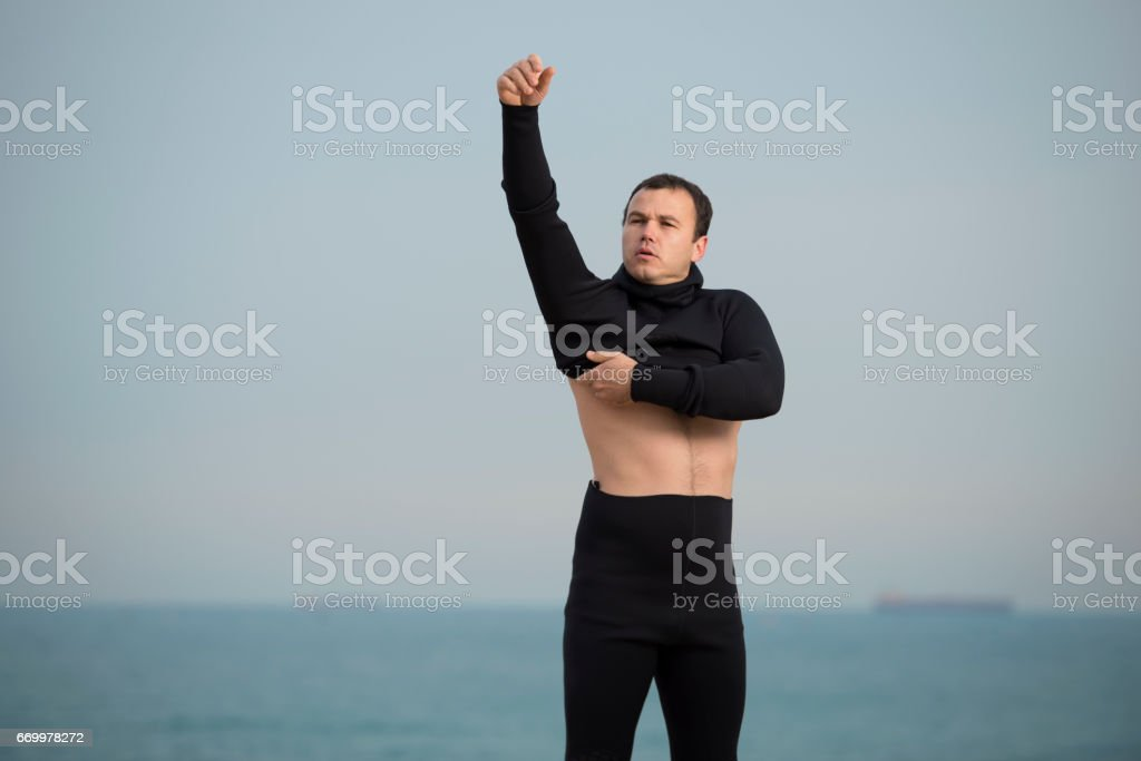 Diver man putting on wetsuit on the sea beach. stock photo