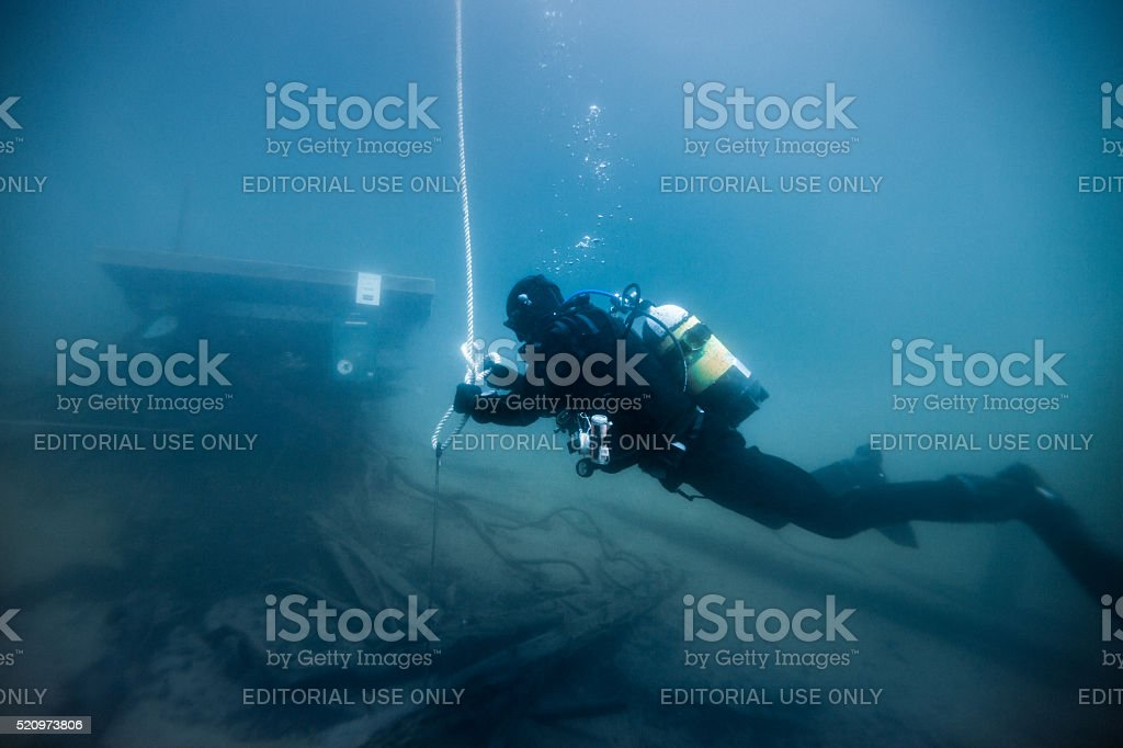 Diver working on dark waters stock photo