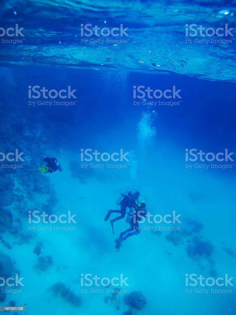Divers in Deep Blue Sea stock photo