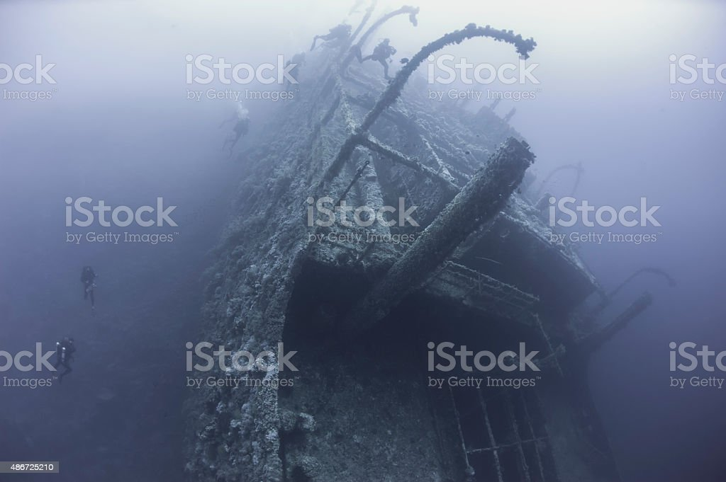 Divers on a deep underwater shipwreck stock photo