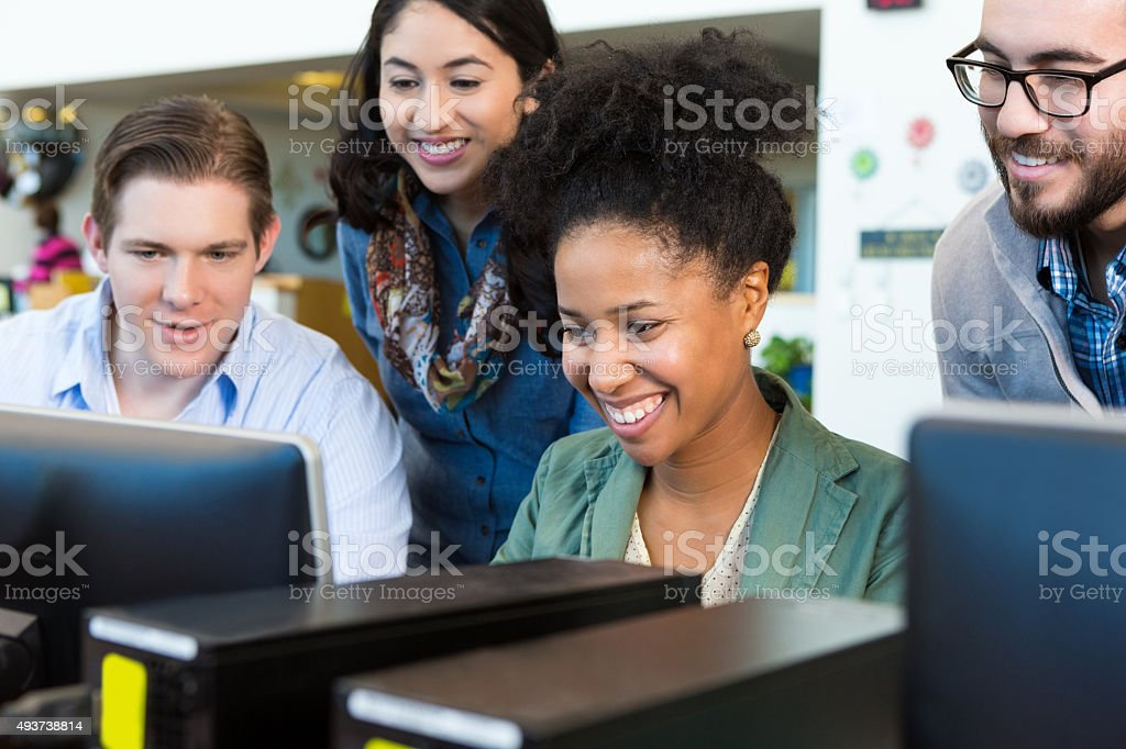 Diverse adult college students using computer together stock photo
