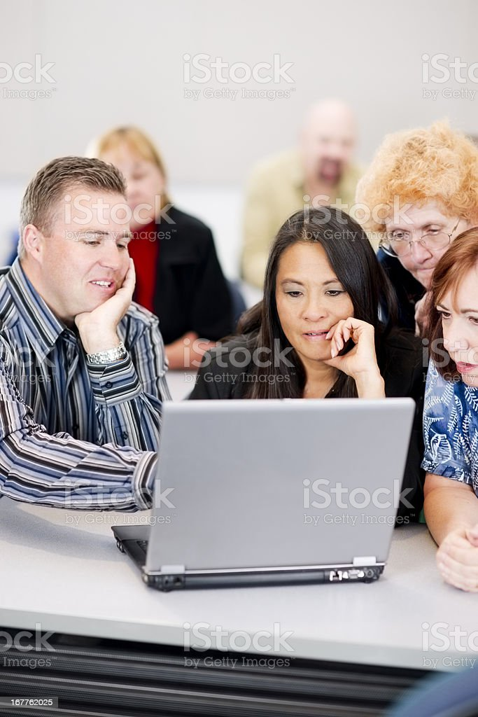 Diverse adult students working in a team on laptop royalty-free stock photo