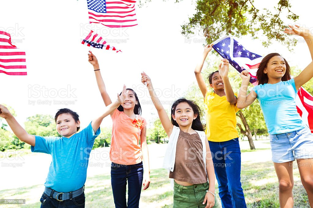 Diverse American kids wave American flags stock photo