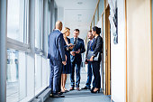 Diverse business group meeting in office corridor