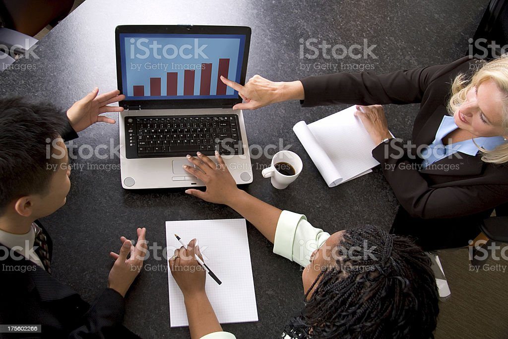 Diverse business team analyzing chart on a laptop stock photo