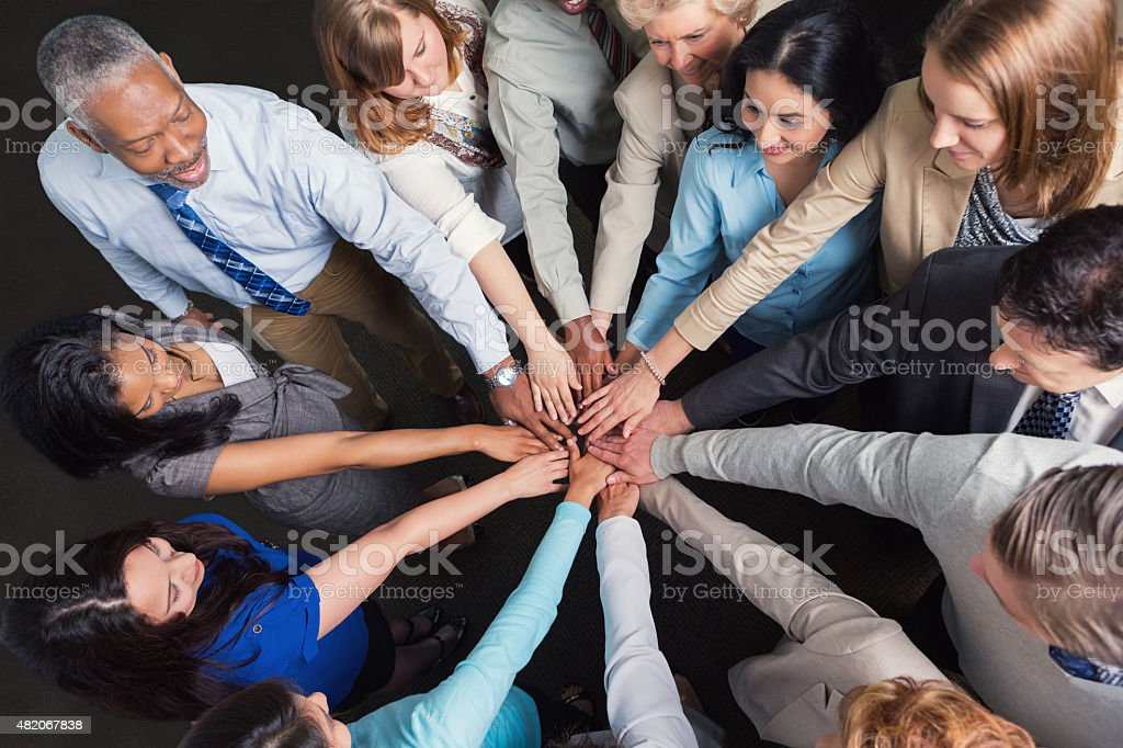 Diverse business team with hands in huddle to celebrate success stock photo