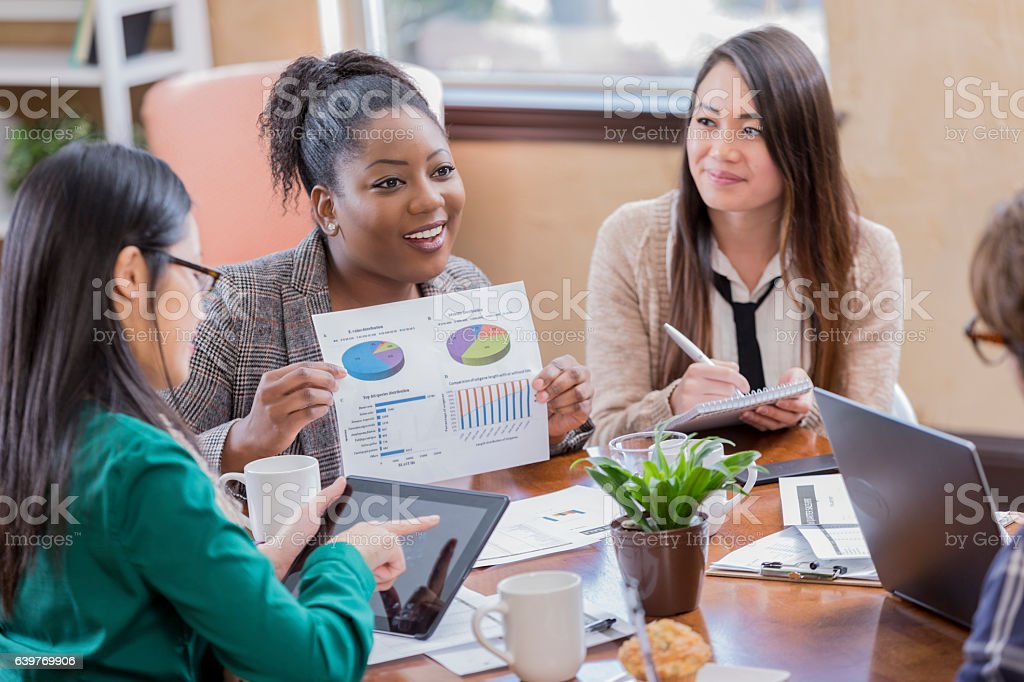 Diverse businesspeople discuss financials during meeting stock photo