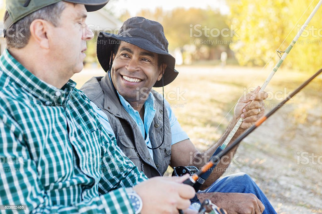 Diverse cheerful friends enjoy fishing together stock photo