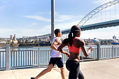 Diverse co-ed couple running together in the city