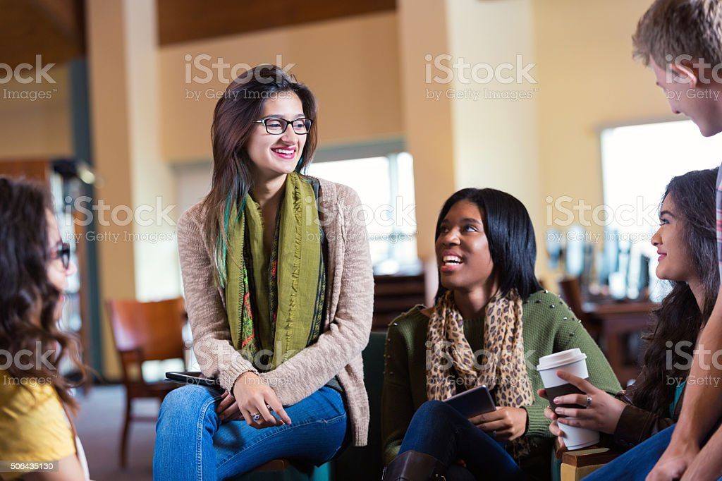 Diverse college students meeting in library or coffee shop stock photo