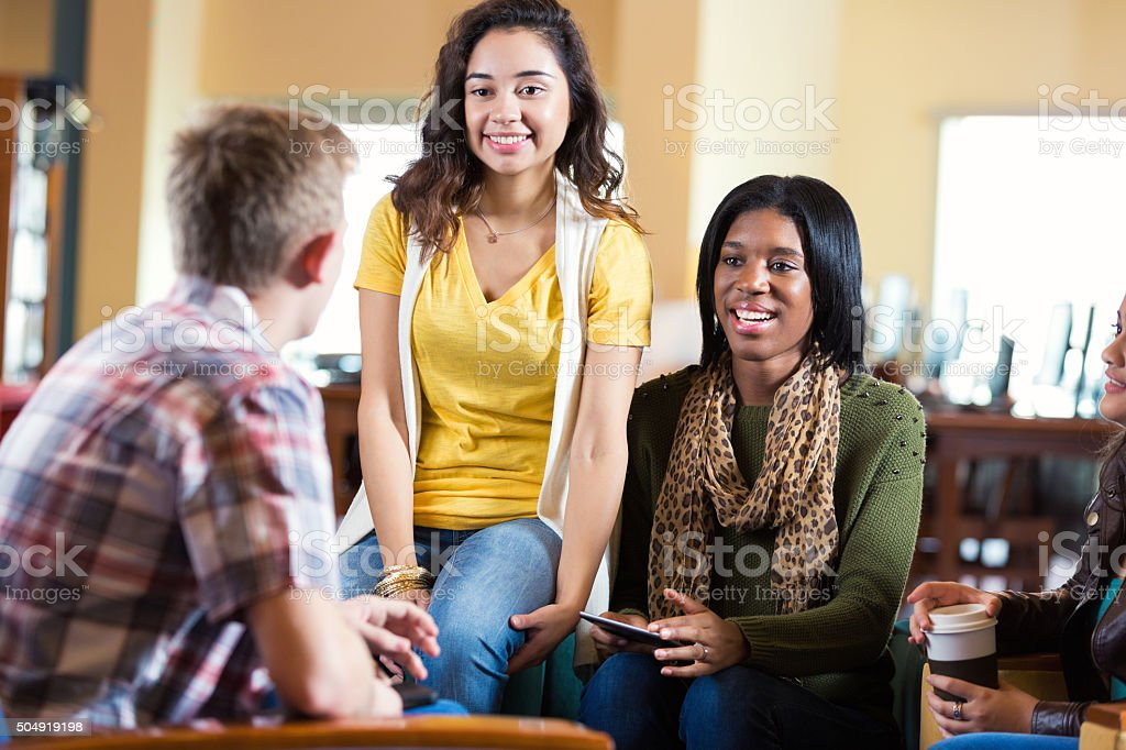 Diverse college students meeting to discuss something in library stock photo