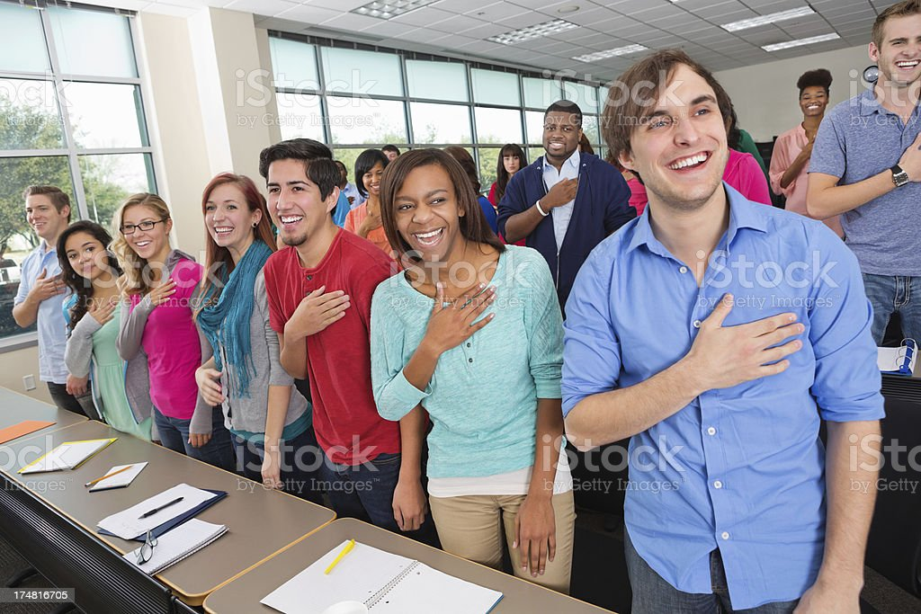 Diverse college students reciting pledge of allegiance in class stock photo