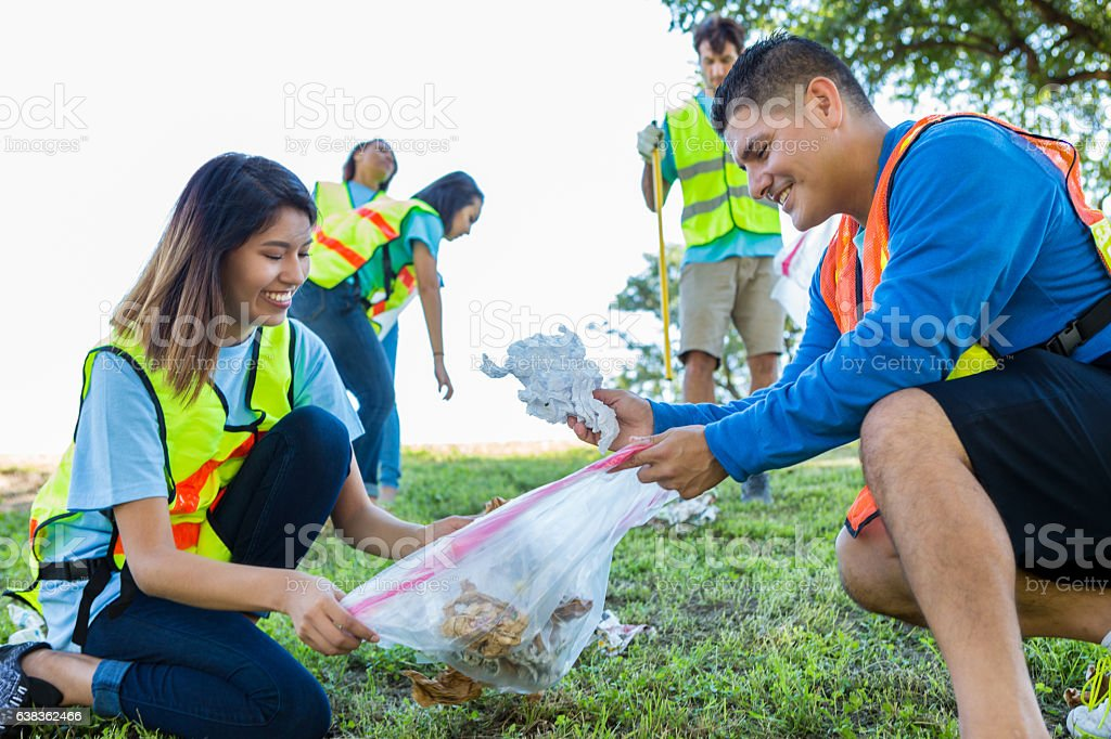 Diverse couple help neighbors clean up community stock photo