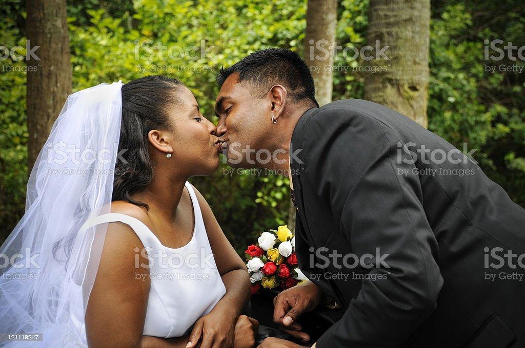 Diverse Couple Sharing a Wedding Kiss royalty-free stock photo