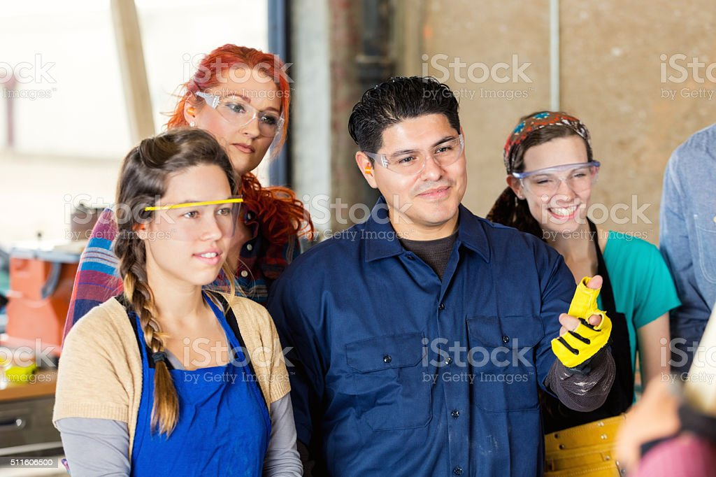 Diverse craftsmen learn about project in workshop stock photo