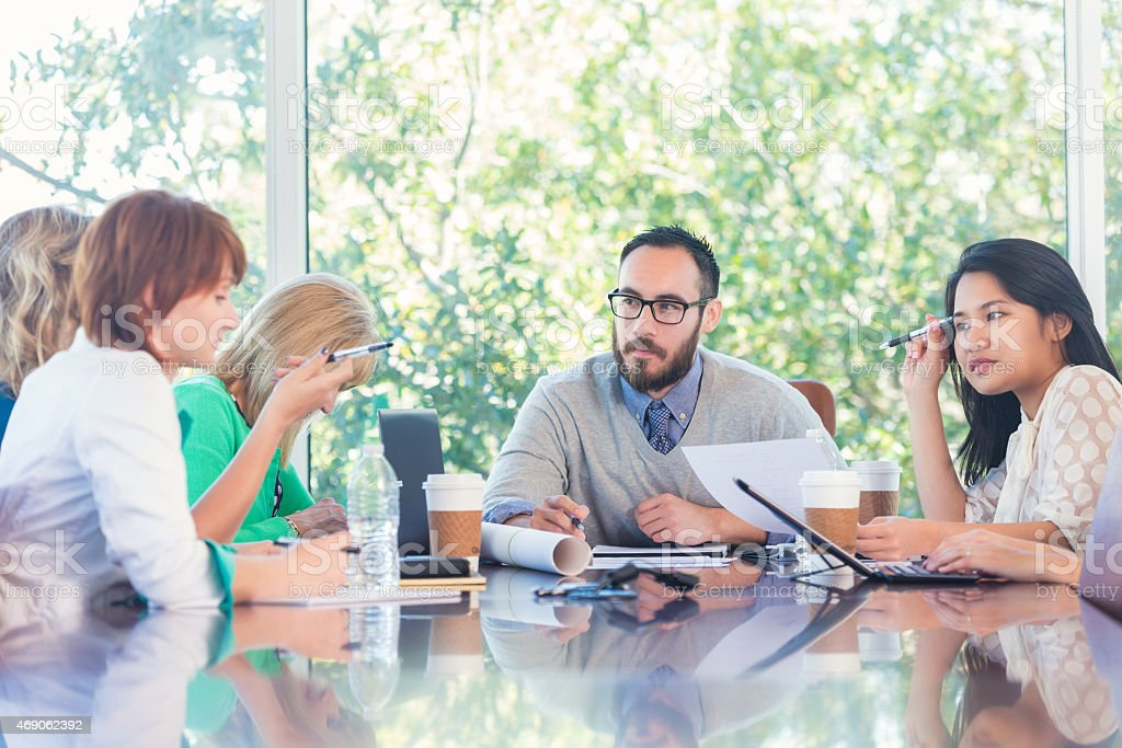 Diverse creative business team discussing project in modern board room stock photo