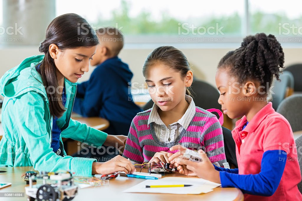 Diverse elementary girls using robotics kit in library makerspace stock photo