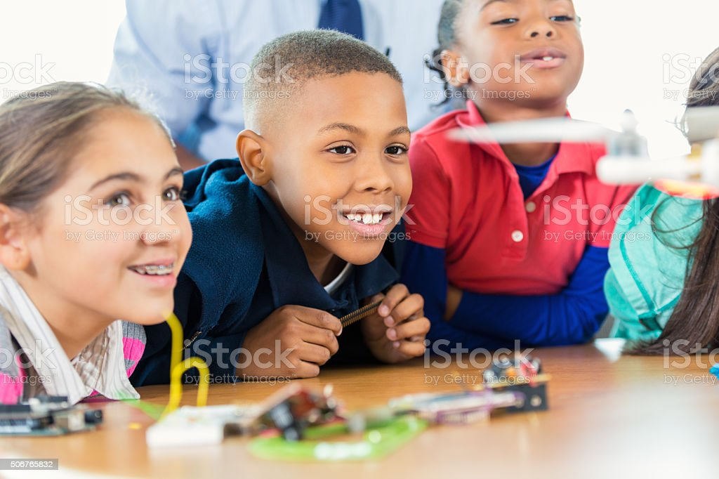 Diverse elementary kids studying drones during science program stock photo