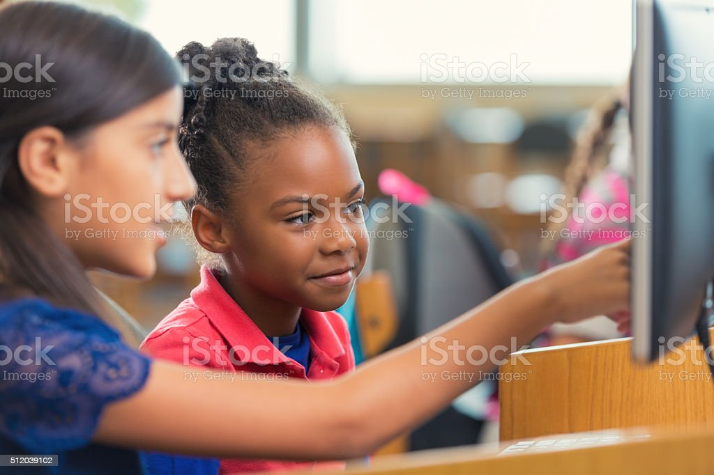 Diverse elementary school girls using computer during class stock photo