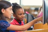 Diverse elementary school girls using computer during class