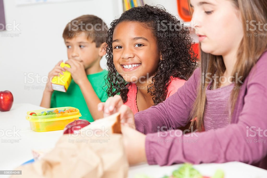 Diverse elementary students eat lunch in classroom stock photo