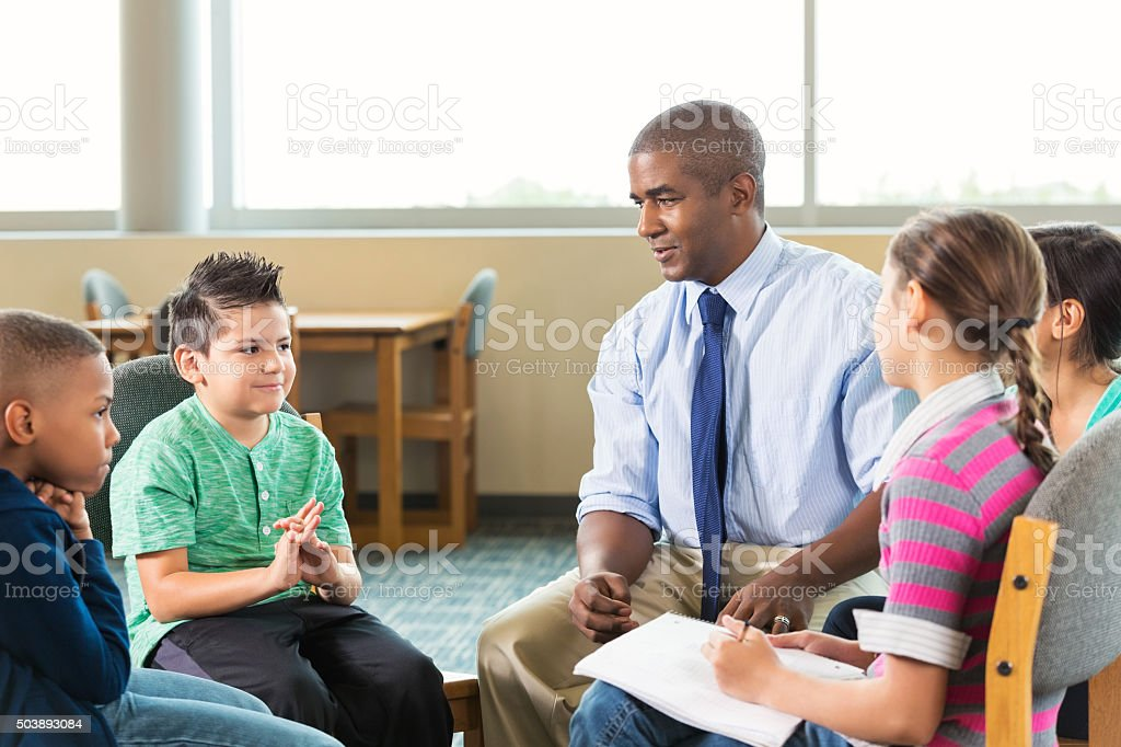 Diverse elementary students meeting with counselor after school stock photo