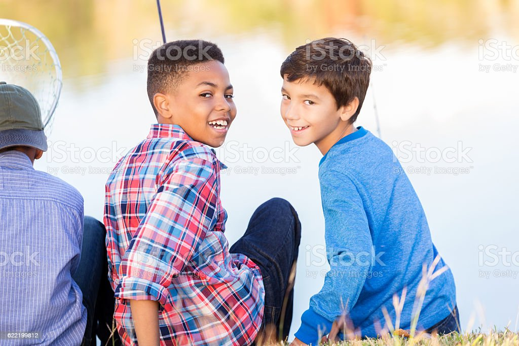 Diverse friends fish together at a local pond stock photo