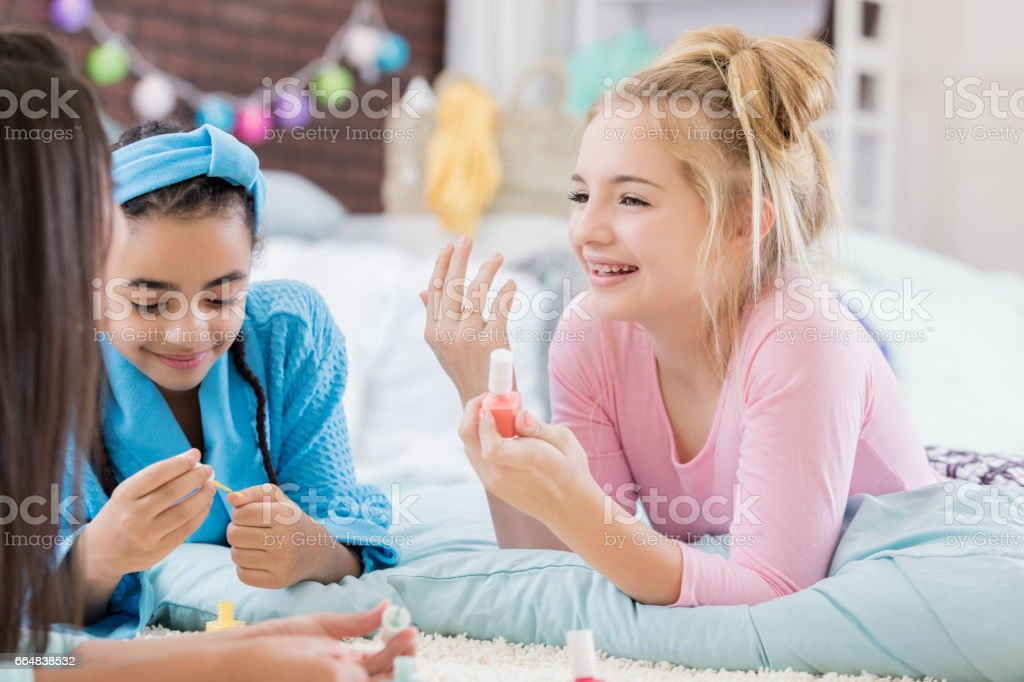 Diverse friends give manicures during sleepover stock photo