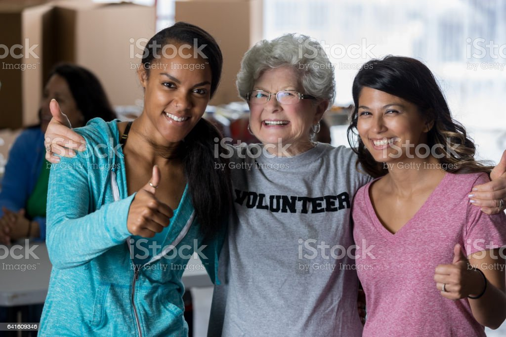 Diverse friends give thumbs up while volunteering together stock photo