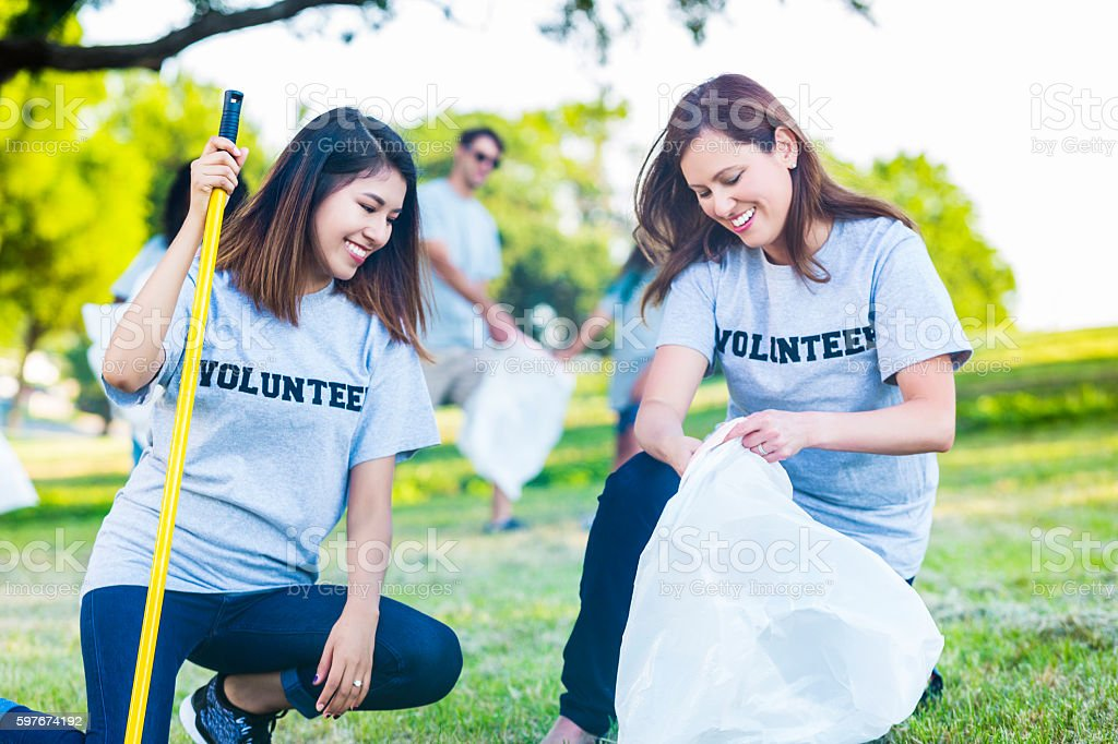 Diverse friends help pick up trash in community park stock photo