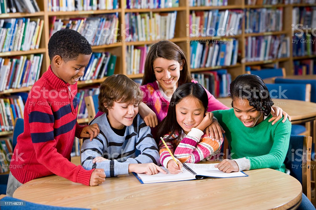 Diverse friends studying together in school library royalty-free stock photo