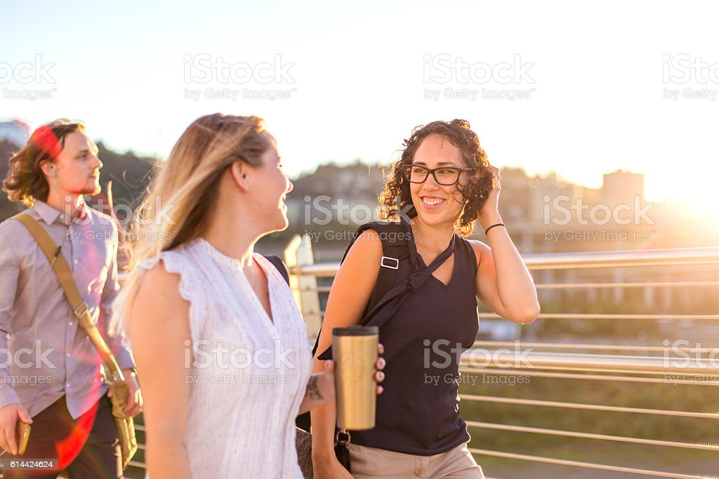 Diverse friends talking during their walking commute to work stock photo