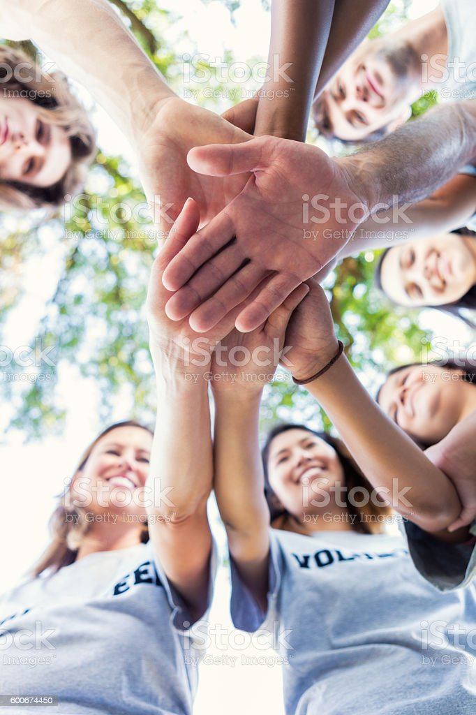 Diverse group of adults outdoors in a huddle stock photo