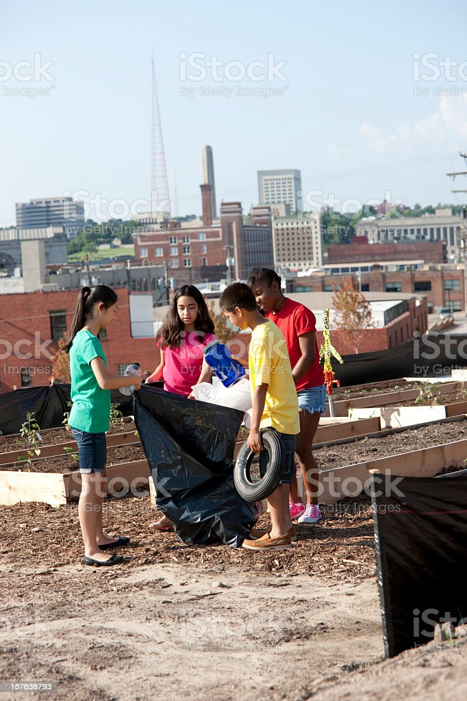 Diverse group of children cleaning up an urban garden royalty-free stock photo
