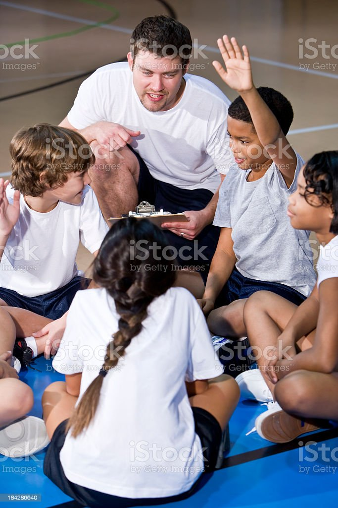 Diverse group of children in gym huddled with coach royalty-free stock photo