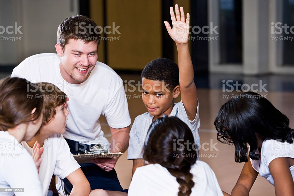 Diverse group of children in gym with coach royalty-free stock photo