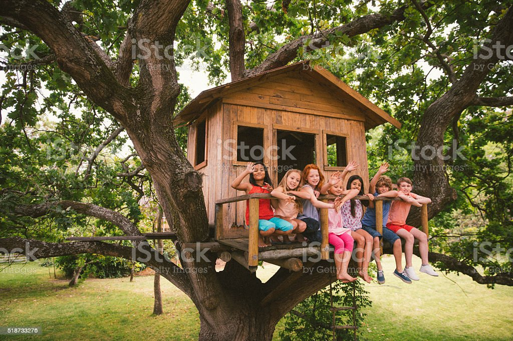 Diverse group of children smiling and waving in a treehouse stock photo