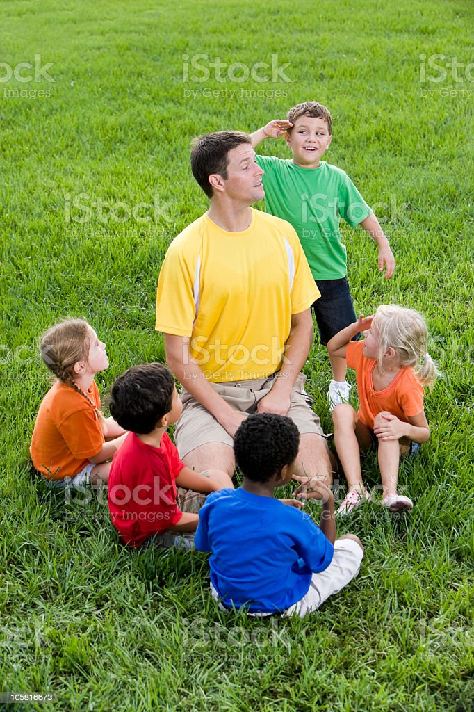 Diverse group of children with summer camp counselor stock photo
