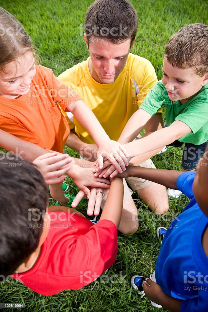 Diverse group of children with summer camp counselor showing tea stock photo