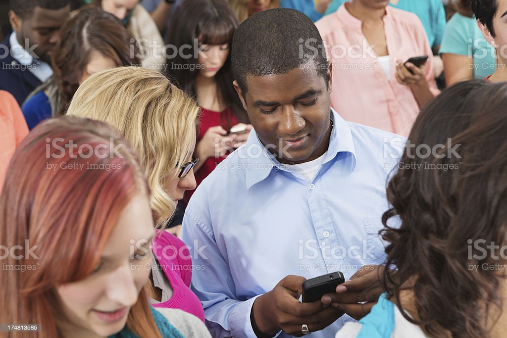 Diverse group of college students using smart phones during event royalty-free stock photo