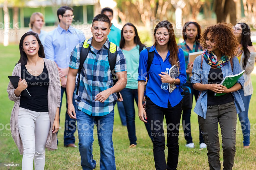 Diverse group of college students walking on beautiful campus stock photo