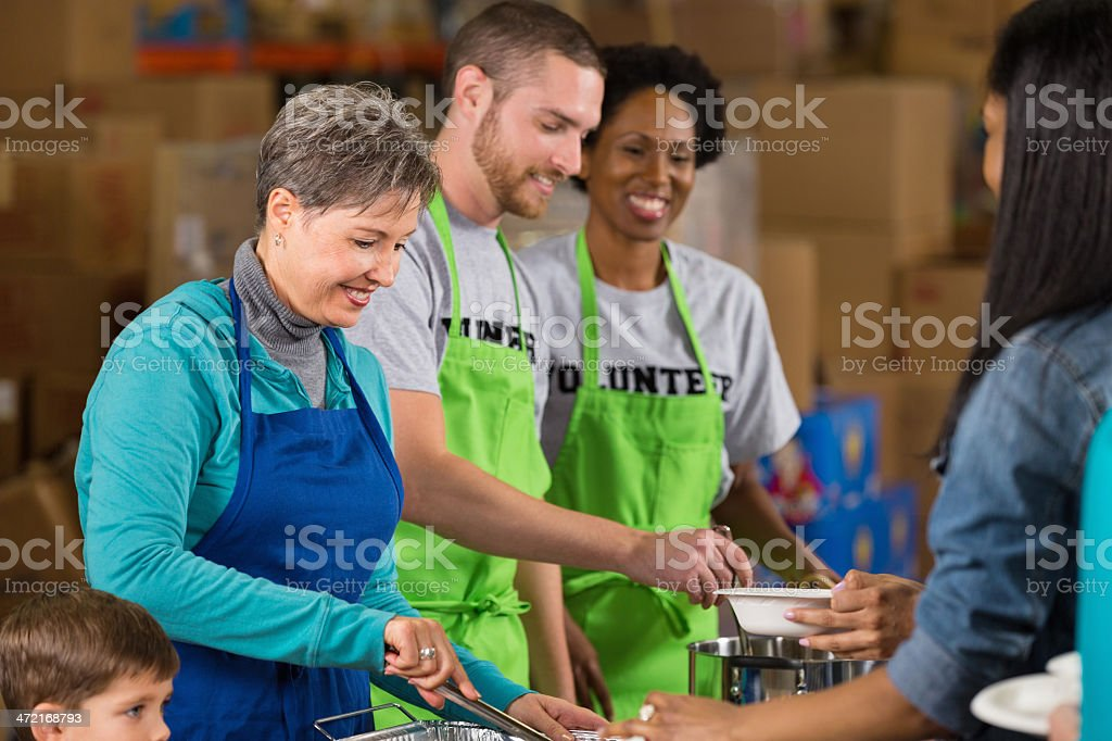 Diverse group of community volunteers serving meal at food bank royalty-free stock photo