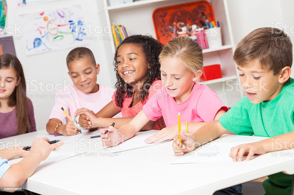 Diverse group of elementary school kids work in class stock photo