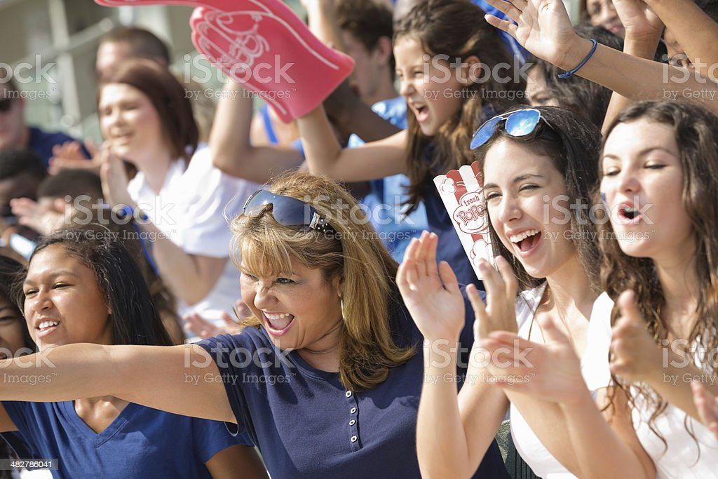Diverse group of excited sports fans cheering from stadium