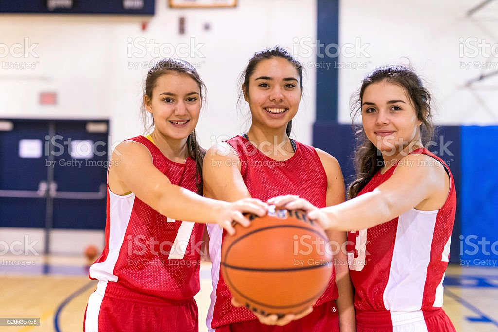 Diverse group of female basketball players holding a basketball stock photo