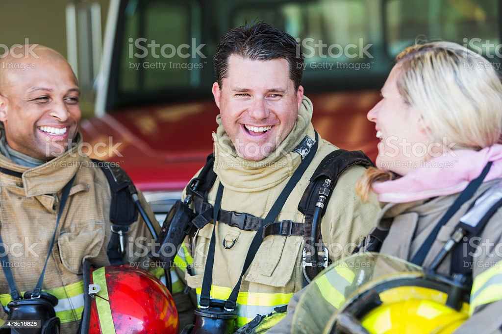 Diverse group of fire fighters at the station talking stock photo