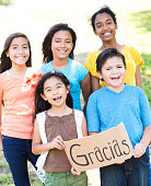 Diverse group of friends hold 'Gracias' sign